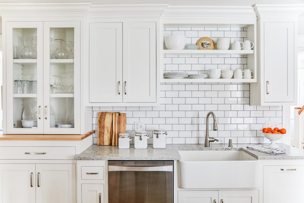 kitchen with white subway tile white cabinets and grey countertops