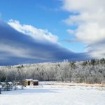 parting skies over snowy field in Maine