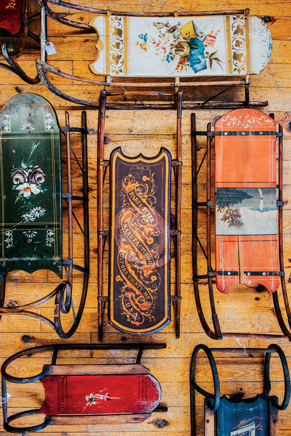 a wall of Victorian painted sleds