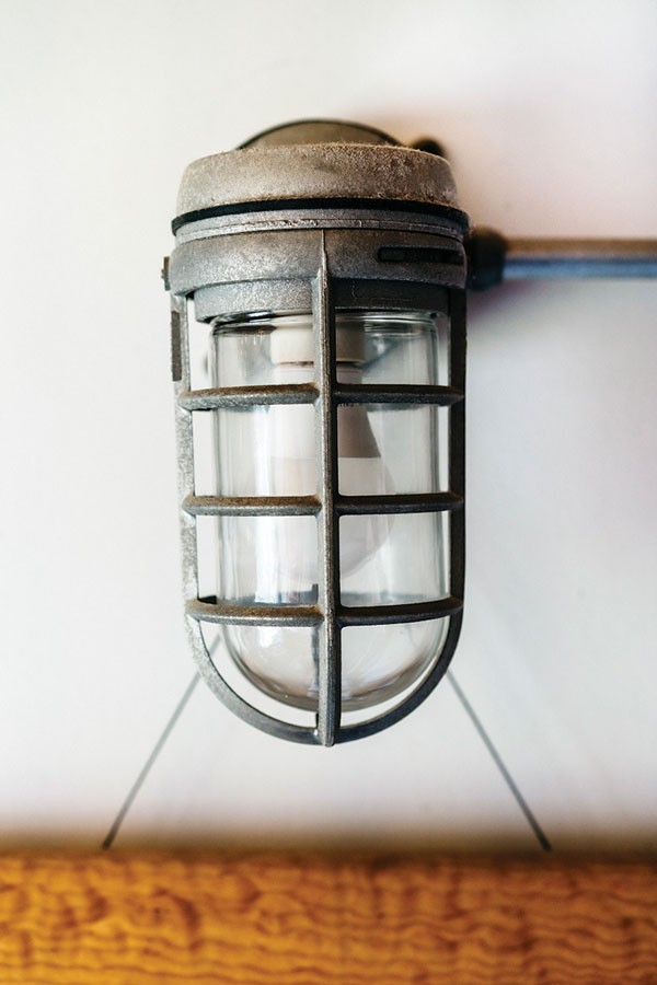 19th-century caged lights, steel-cleat handles on a steep, polished-wood rear staircase, and a stainless-steel shower from a submarine.