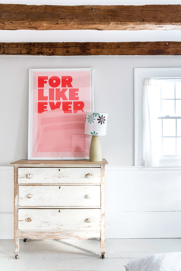 a silkscreened print rests atop a vintage bureau in the master bedroom