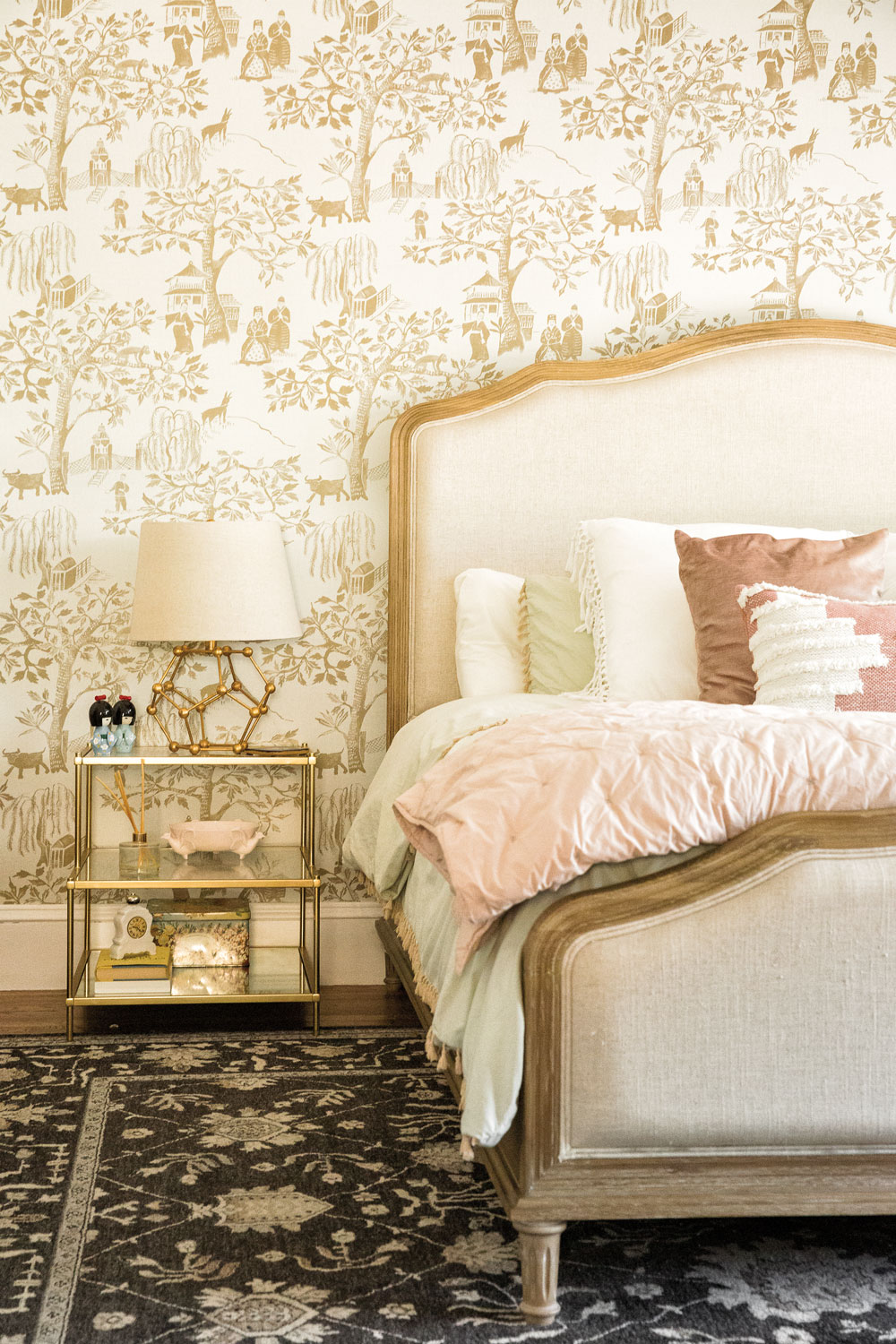 Toile wallpaper adorns a master bedroom accent wall. A metal lamp and nightstand reference the lines on the Parisian-style bed.
