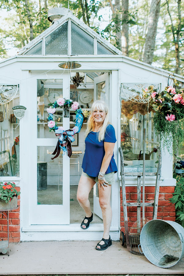 Pam Allen steps out of the greenhouse that Eric built with department-store glass shelving and discarded windows