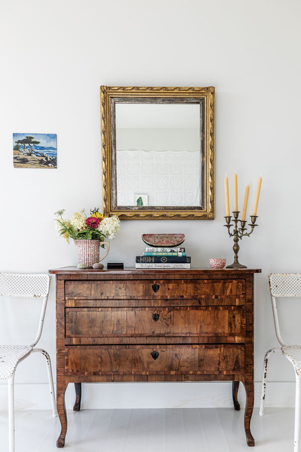 A burled-fruitwood chest and gilded mirror, flanked with 1950s French metal chairs from Marston House