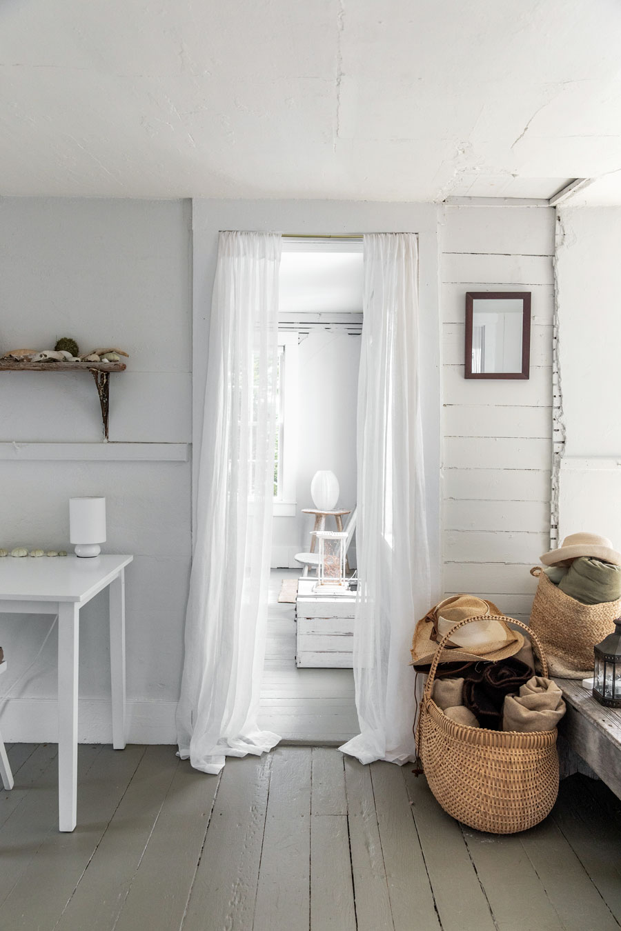 Alabaster walls, sea-smoke floors, and sheer curtains create an ethereal vibe in a guest/sitting room, minimally furnished with beach and thrift store finds.