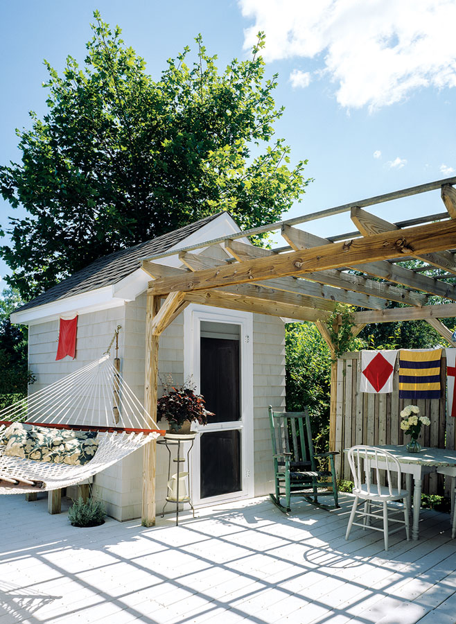 deck that links the mansard tiny home to a shed and bunkhouse.