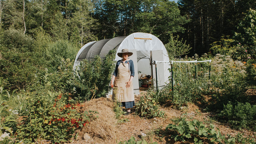 Amy Pollien standing in front of her Bar Harbor garden's hoop house