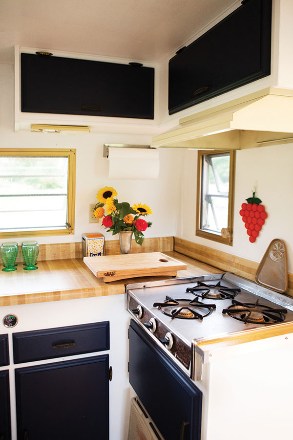 the 1973 Shasta 1400 camper's original cabinetry, laminate countertops, and appliances