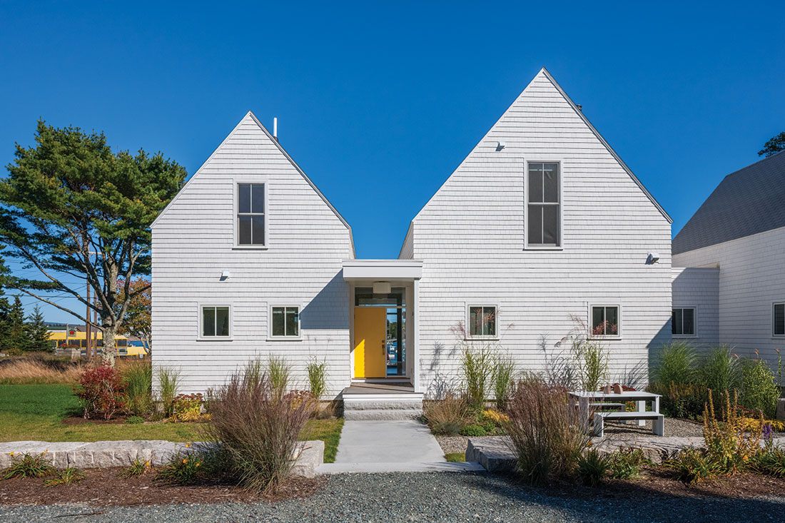 yellow door on a gabled retreat designed by WMH Architects in Bernard Maine