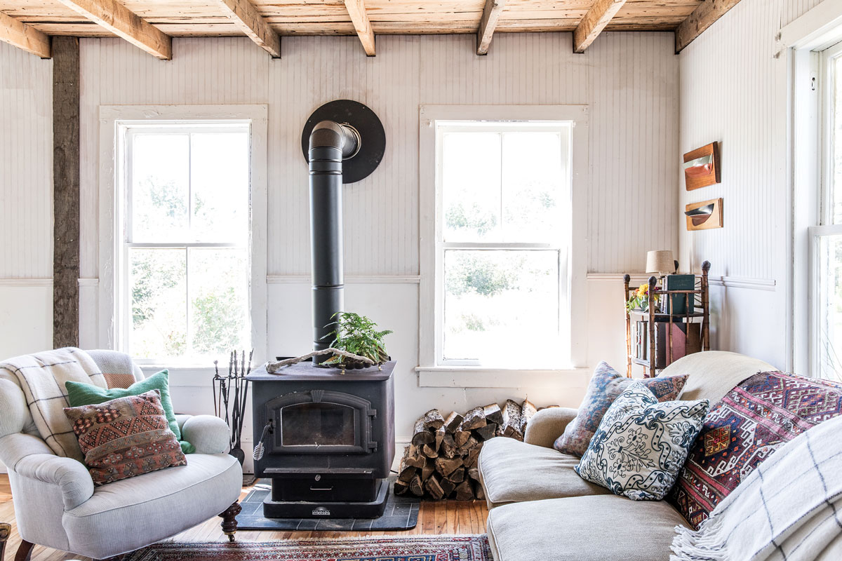In the living room, Kilim pillows add subtle punch to a vintage chenille Ralph Lauren sofa, spotted on Craigslist, and a reupholstered English roll-arm chair. The woodstove, another Craigslist find, was installed by the homeowners.