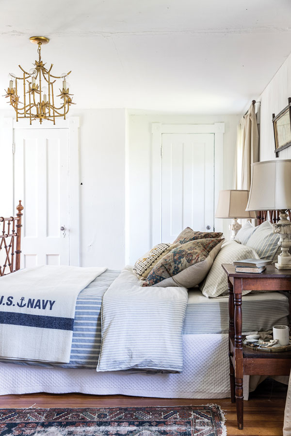 in the master bedroom, an antique brass chandelier from Chairish complements a Chinoiserie bed found on Craigslist.