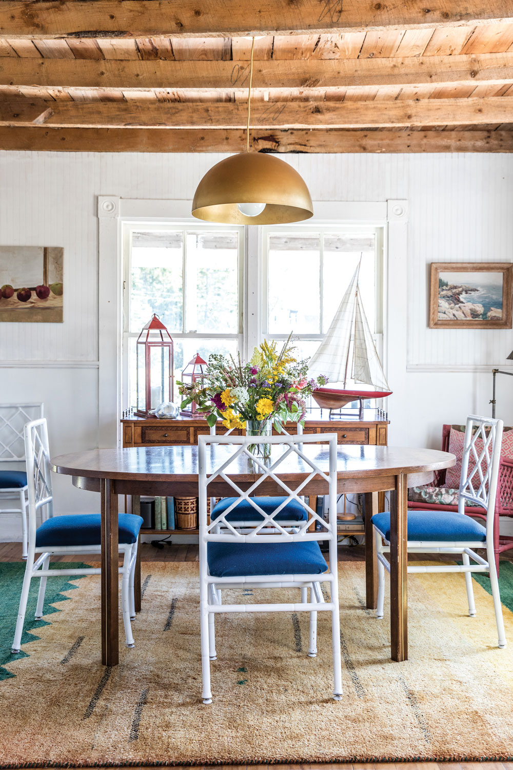 A Target brass pendant pulls the warmth of the exposed beams into the dining room, where salvaged metal chairs, a hand-me-down, mid-century table, and yard-sale oil paintings create an elegant, lived-in look.