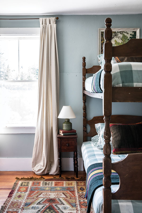 In the couple's son's room, mid-century bunk beds with Target plaid duvet covers and throw pillows made by Salway from wool saddlebags are a durable home base.