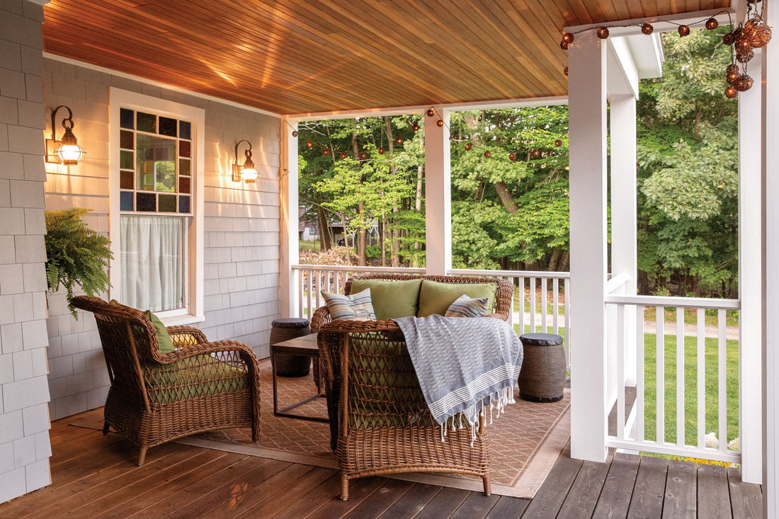 Cushy Lowes wicker seats and a rug from Homegoods create a snug living area on Michele and Mark Zajkowski's Great Diamond Island porch.