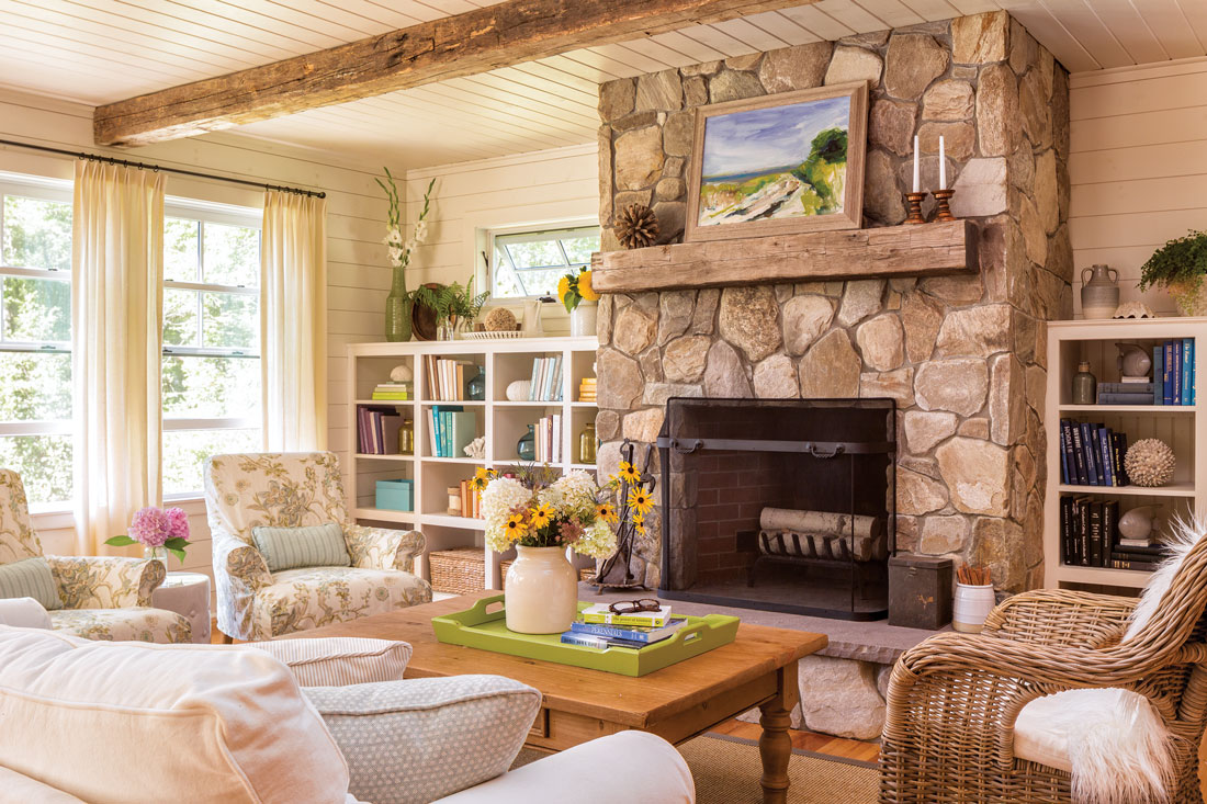 A Maryann Didriksen seascape punctuates the living room fireplace, crafted by South Portland's CMP Stone Masonry; the barn beams are from SoPo's Rousseau Reclaimed and the slipcovered seating from Dwellings and Falmouth's Simply Home.