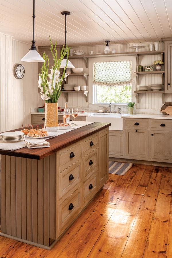 Beadboard paneling; cabinets and shelving in a mottled, glazed finish; a rich walnut island top; subtly veined Imperial Danby countertop; and knotty-pine floor energize the kitchen's neutral palette.