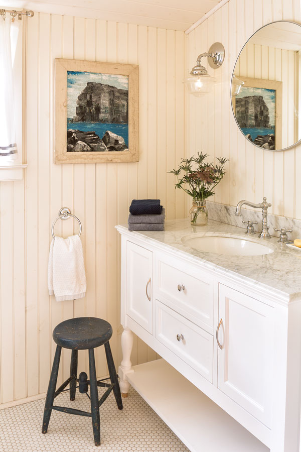 In the upstairs bath, a Wayfair Carrara-marble-topped vanity picks up the variegated grays in an antique painting.