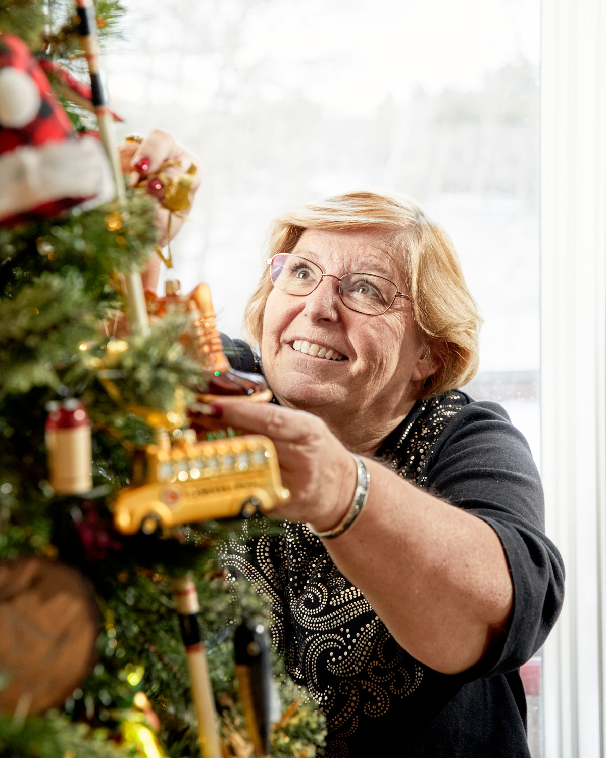 Marianne Kane decorating one of her many Christmas trees