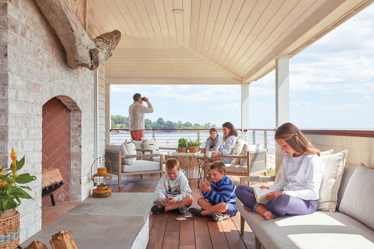 The Hartz clan gathers on the wraparound porch, furnished with a fireplace adorned with a driftwood mantel, a recycled wood ombré coffee table, and teak upholstered seating.