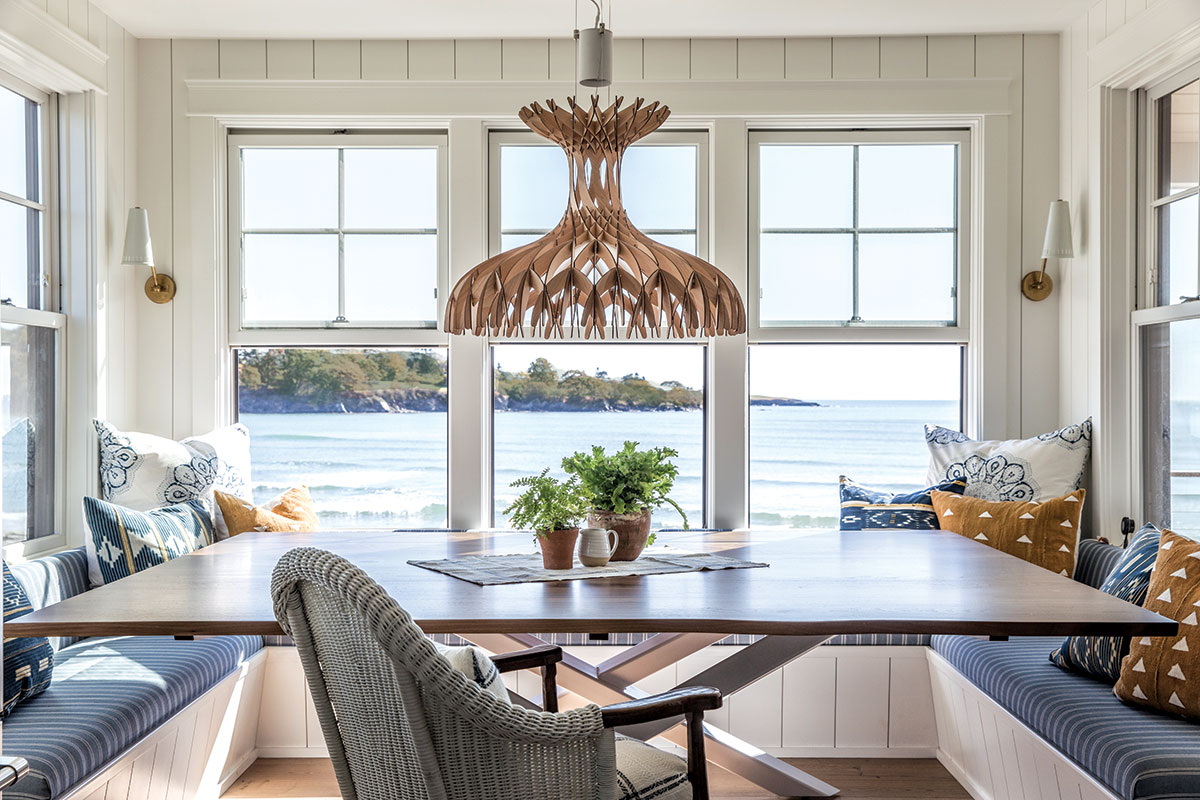 In the kitchen, a banquette hugs a custom walnut table by Kennebunkport's Huston & Company crowned with a balsa-wood pendant.