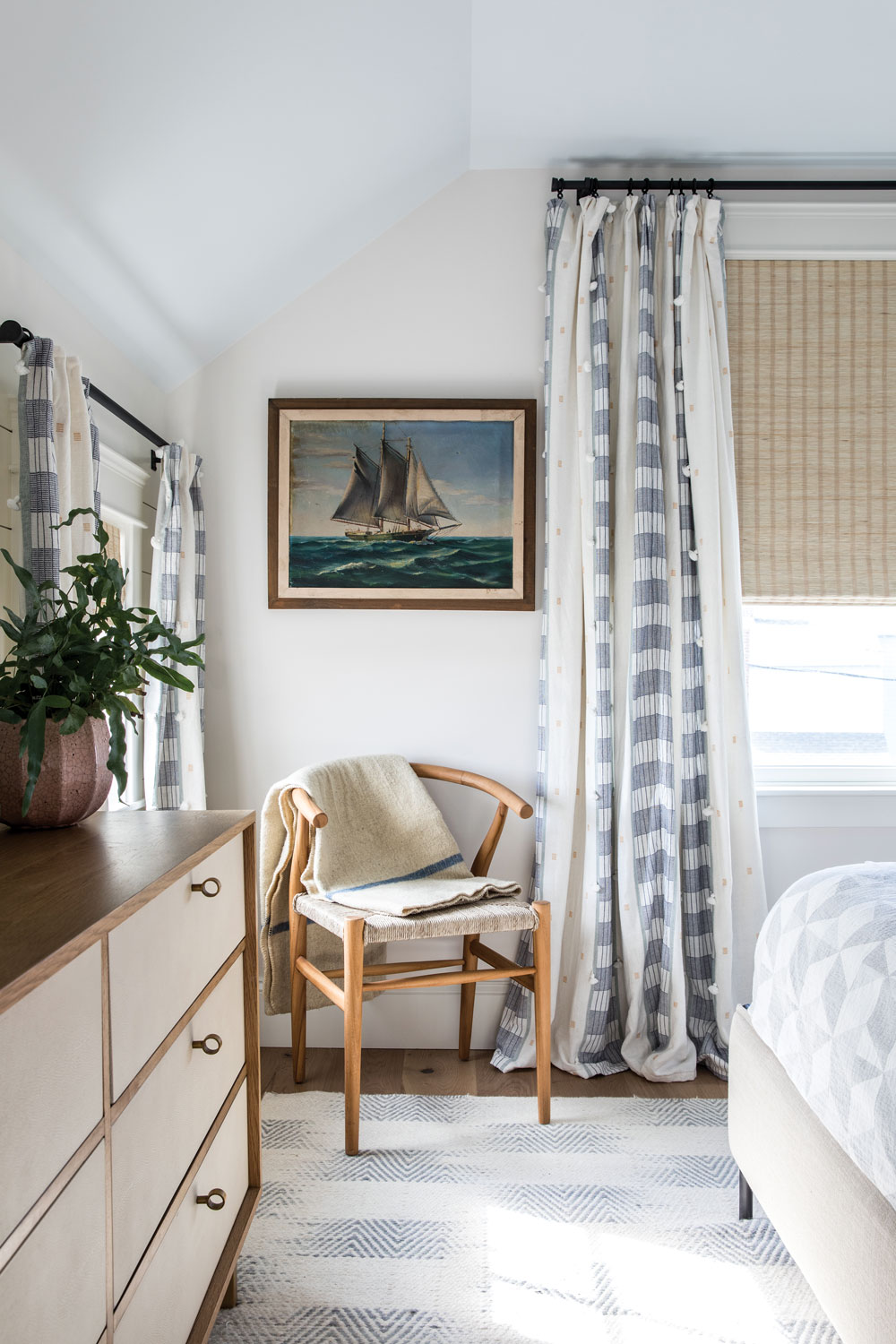 In the guest room, Yarmouth designer Nicola Manganello paired an antique ship's portrait from Massachusetts's Brimfield flea market with a Wishbone chair and billowy Anthropologie draperies.