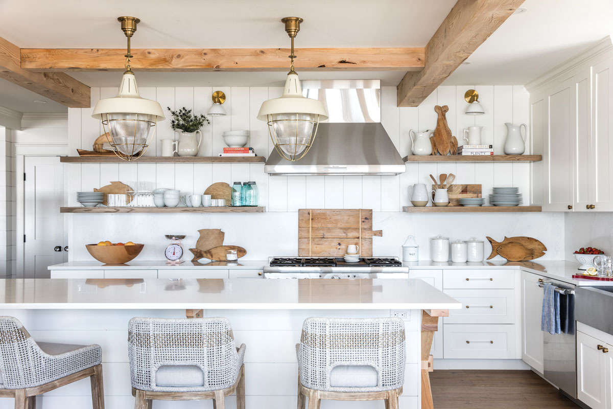 Salvaged hemlock beams, oak shelving and X-shape designs on the ends of the island, teak stools, and ivory enameled- metal Visual Comfort pendants warm the kitchen's frosty palette.