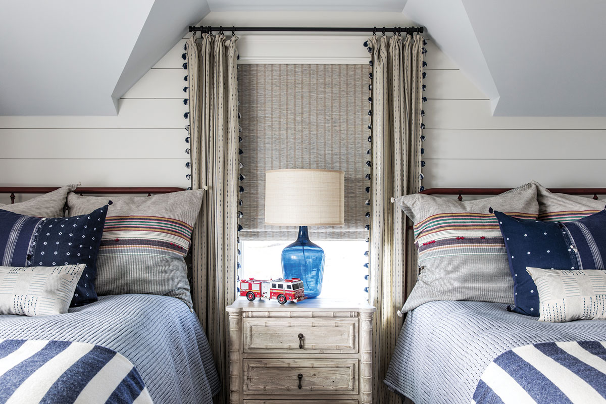 Tasseled Anthropologie draperies, a reclaimed wood table in a mottled, whitewash finish, and striped bedding from Nicola's Home give the bunkroom a playful vibe.