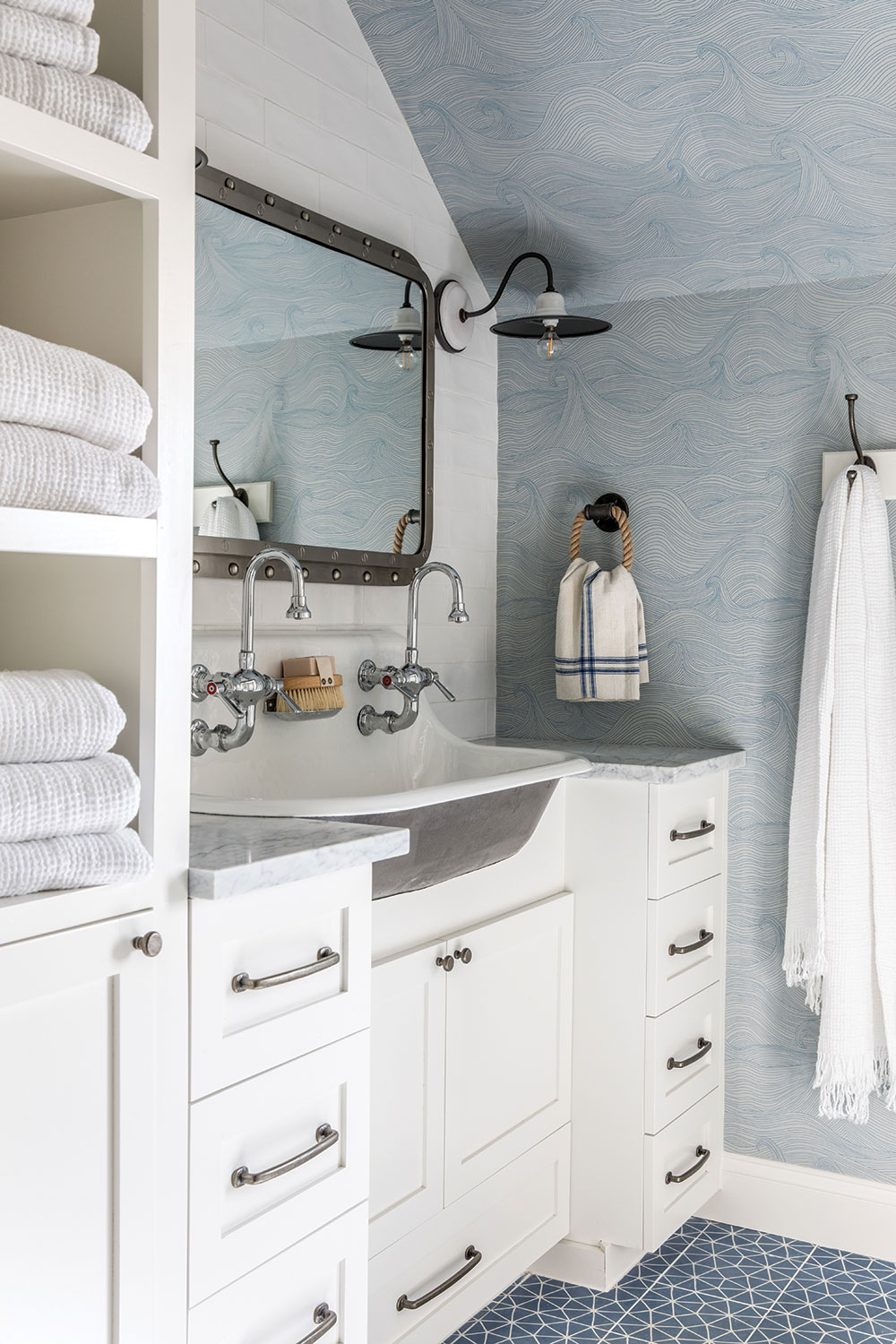 The kids' bath combines a Kohler cast-iron trough sink with Abigail Edwards's Seascape wallpaper and geometric floor tile.