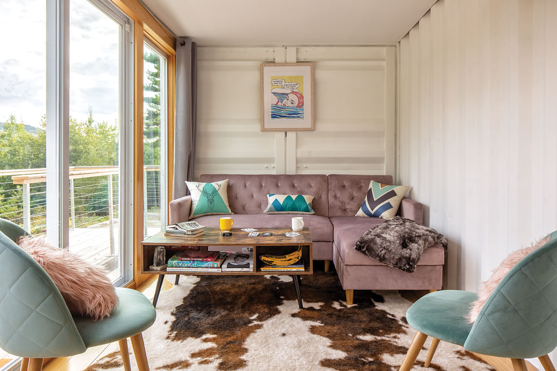 the walls of the shipping container are visible in the home's living room