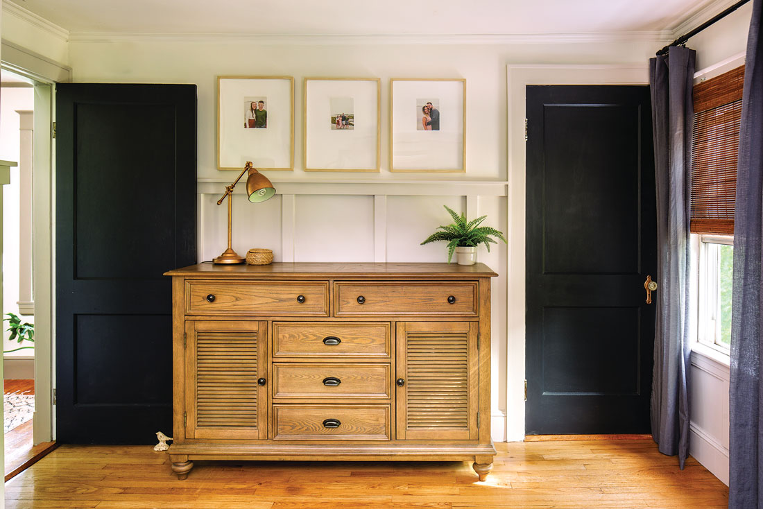 Doors painted Benjamin Moore's Black Ink frame a dresser from Facebook Marketplace and board-and-batten paneling, finished in Behr's Mocha Light,