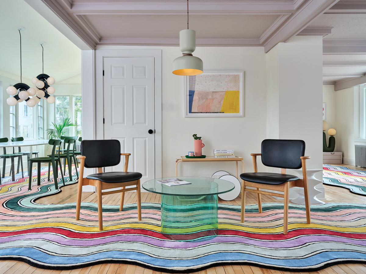 In the sitting room of Kennebunk's Pieces Homes Airbnb, lavender-gray Backdrop ceiling paint, art by Ashley Peifer, and a glass-and-acrylic Pieces table speak to the shades in the company's signature rainbow rug.