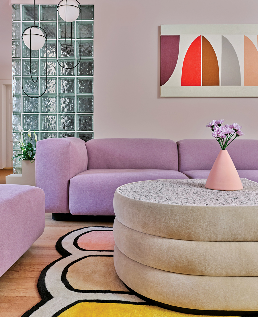 Rounded forms reign in the family room, featuring a Vitra sofa, Kimmy Quillin acrylic, and Pieces coffee table and rug.