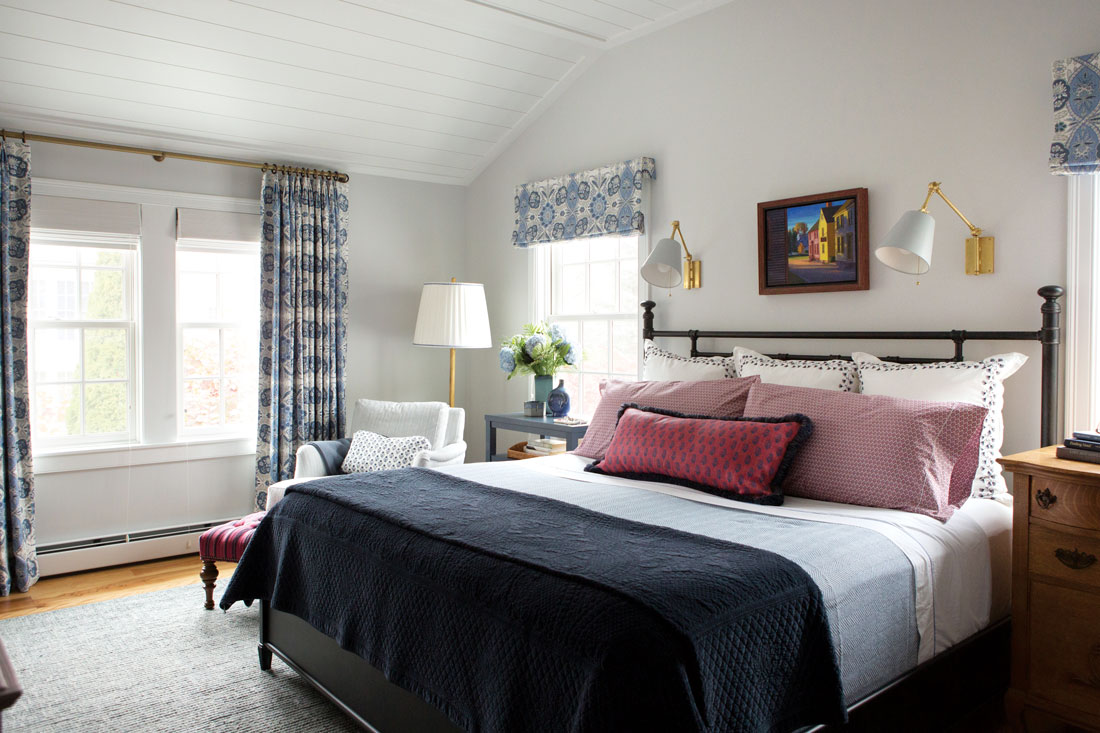 Paintings by Carol Aronson-Shore and Kennebunk's Deborah Randall distill the palette in this bedroom/office, which blends printed fabrics by Cowtan & Tout, Lee Jofa, Peter Dunham Textiles, and Schumacher with a painted nightstand by Kennebunk's Americana Workshop and Visual Comfort lighting.