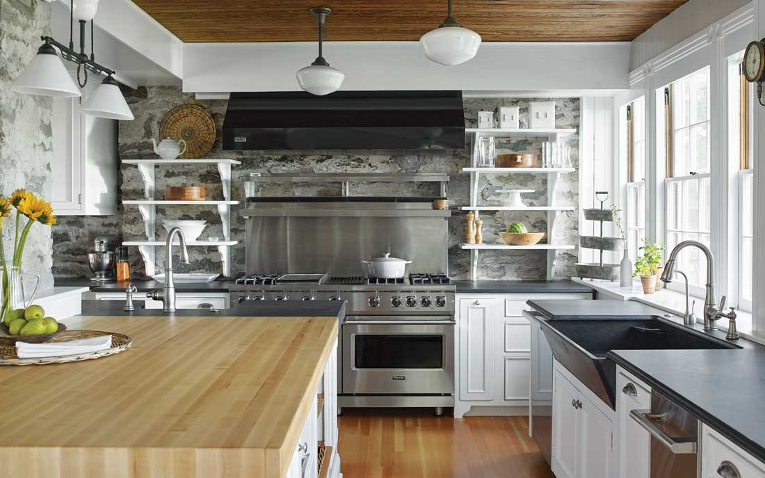 The home's stone foundation backdrops open shelving in the kitchen, which sports its original slate sink and butcher-block island top.