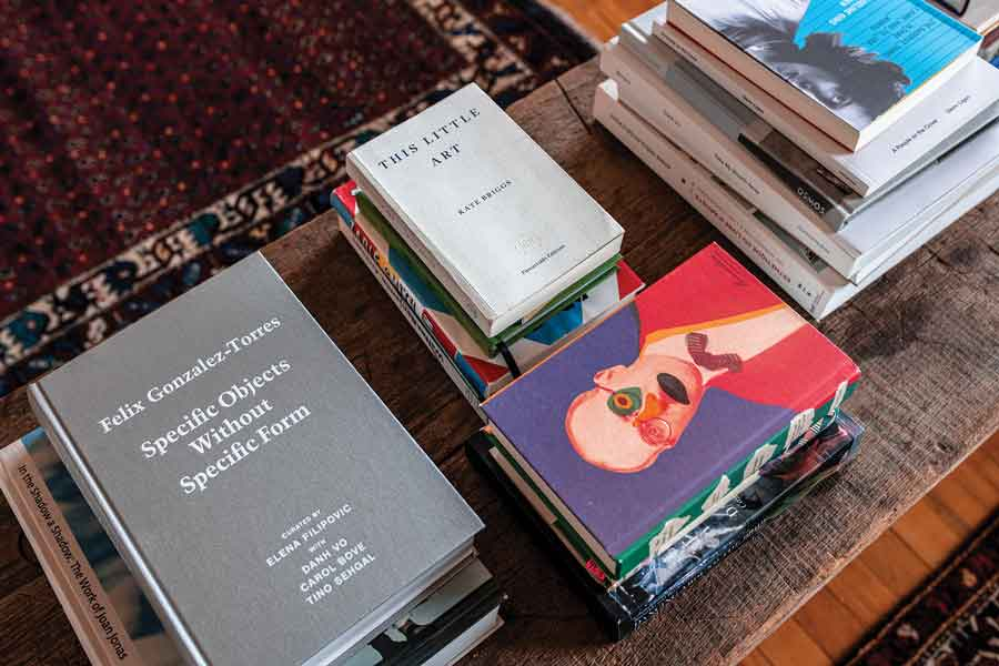 piles and piles of art books on a coffee table