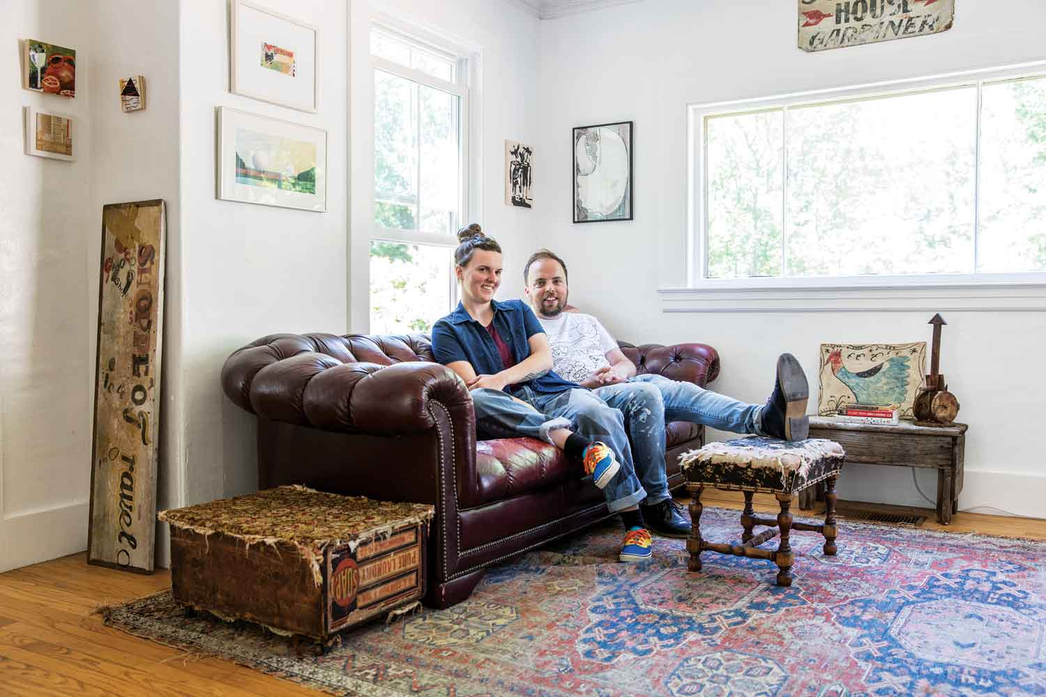 In the living room, the footrest is fraying, the rug is faded, and the end table is a soap box a previous owner outfitted with casters and a hinged, carpeted lid.