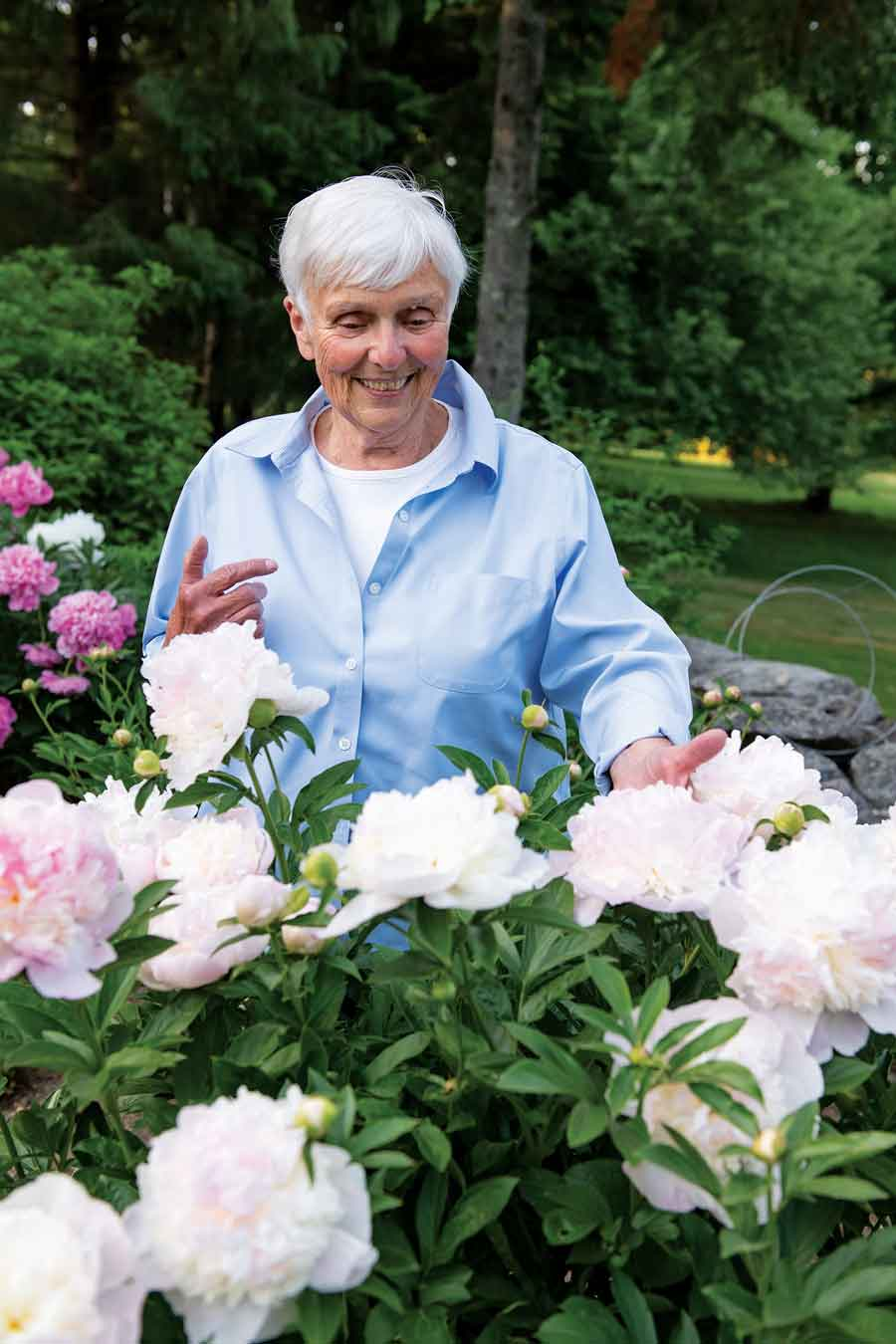Linda Faatz takes a moment to enjoy a few of the many peonies that ring the Courtyard Garden.