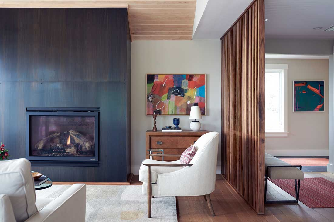 Acustom walnut screen separates Louis Kaucic and Billy Merritt's Cape Elizabeth great room — furnished with a blackened-steel fireplace, wool-and-silk carpet