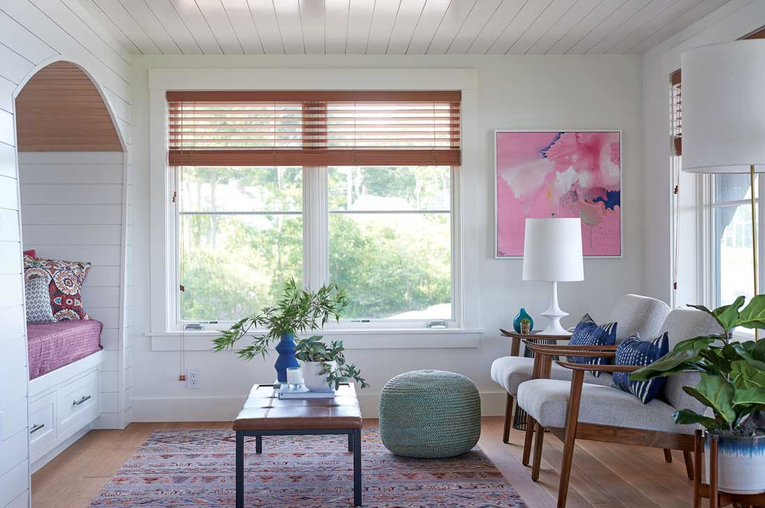 Pops of pink in an abstract painting and Peter Dunham fabrics warm the lower-level living area.