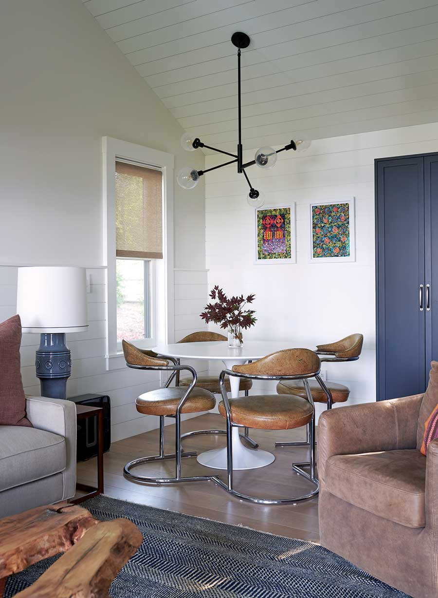 Works by Cape Elizabeth's Missy Dunaway crown a Saarinen table surrounded with vintage leather chairs in a guesthouse dining area.