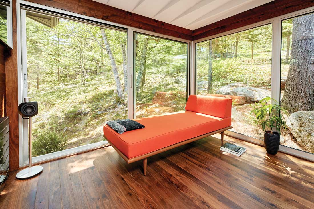 a glassed-in sanctuary with walnut flooring, and a George Nelson daybed