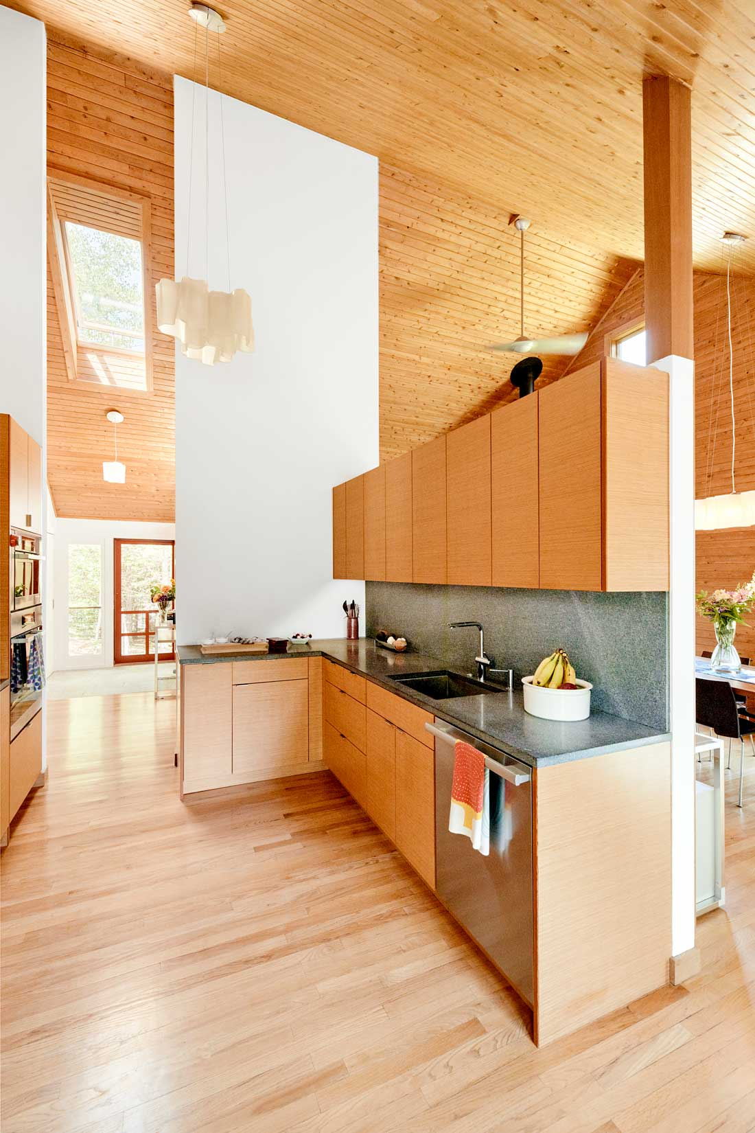 vertical-grain fir contrasts with a Morning Mist granite countertop and backsplash from Freshwater Stone and the home's knotty-cedar paneling