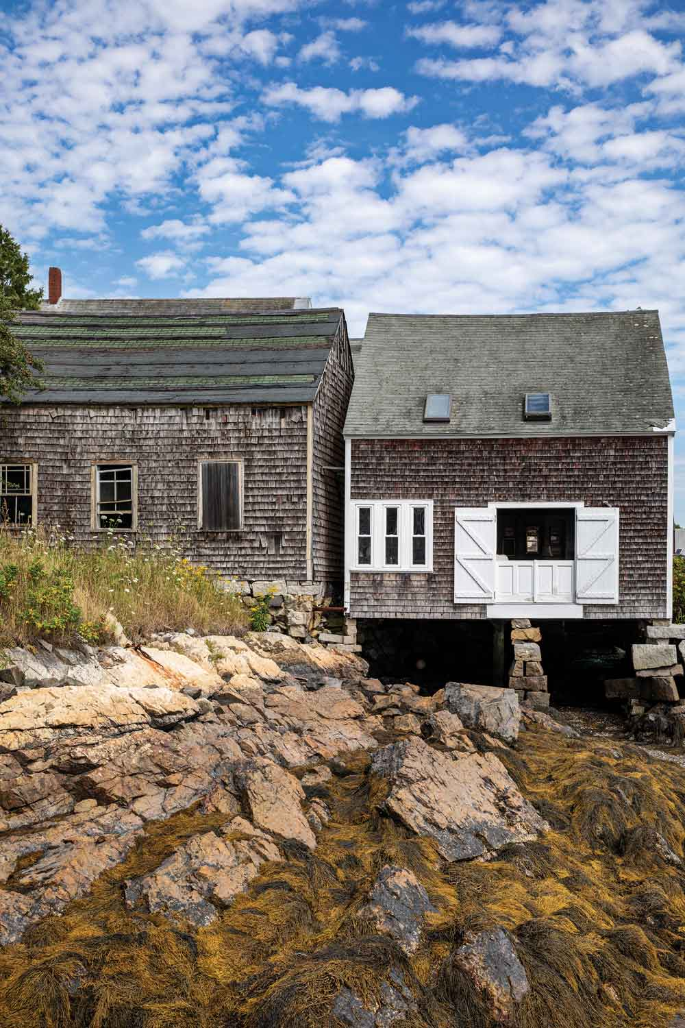 The two-room — one up, one down — cottage rests entirely on pilings; the island's former icehouse sits behind it