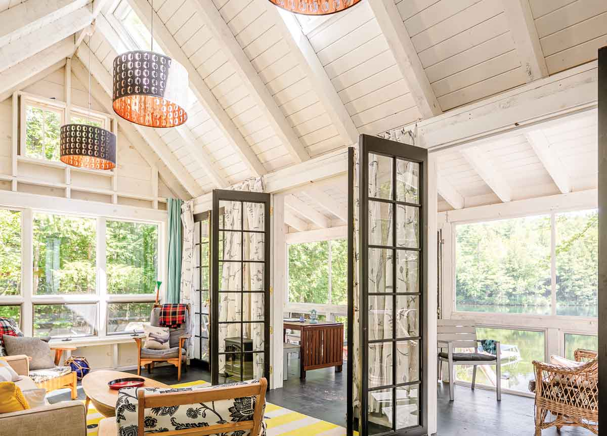 A decade ago, Birlem purchased the living room's French doors for $10 apiece on Craigslist, figuring she'd eventually find a place for them. Fanciful IKEA-fabric curtains provide privacy at night. On the screened porch, a wooden table expands to seat 12.