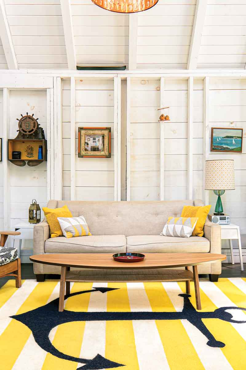 A Craigslist rug, surfboard-shaped coffee table, and thrift-store art give the living room a nautical point of view; the sofa is from Wayfair and Birlem found the lampshade at the Cape Elizabeth Swap Shop.