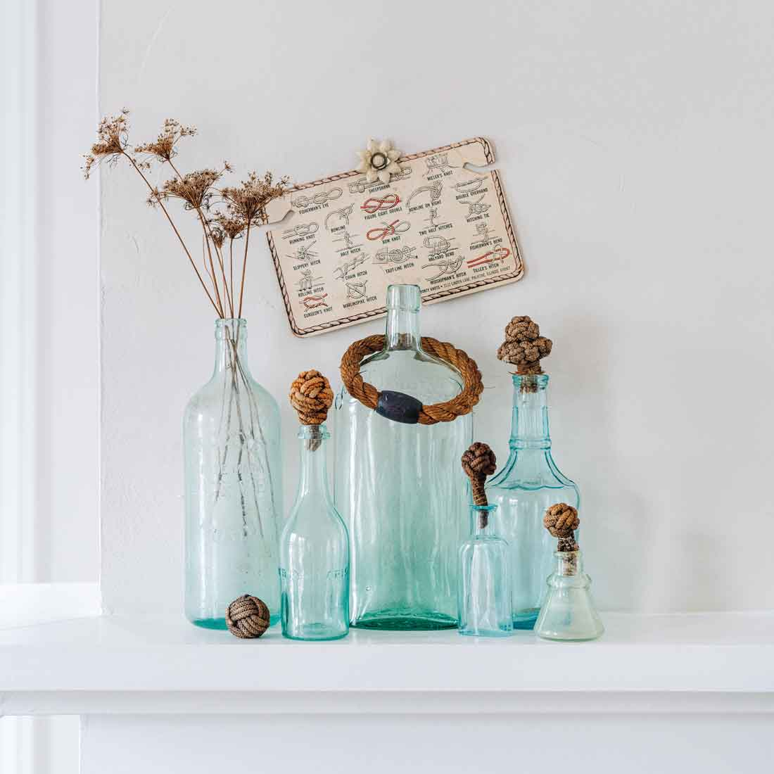 Antique rope knots and part of an old ring-toss game give weight to ethereal glass bottles; dried Queen Anne's lace and a knot-tying guide, held with a vintage curtain push pin, add height.