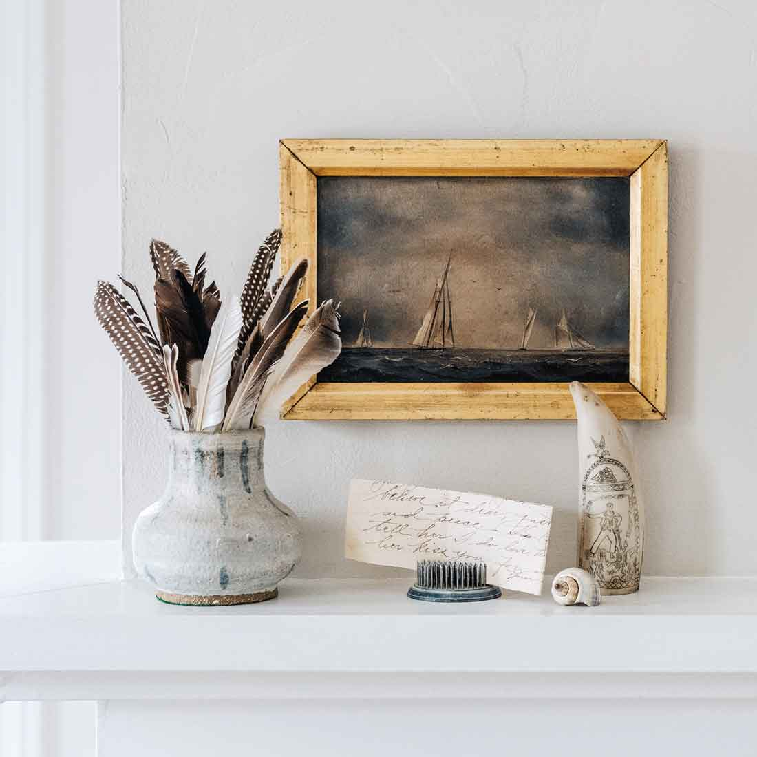 Donovan typically starts with an antique seascape, which she often reframes. A jar of crafts store feathers elongates the tableau, while a scrimshaw replica and letter in an antique flower frog create balance.