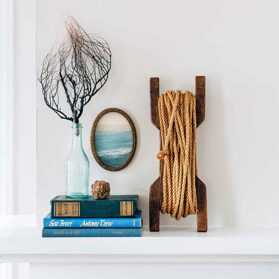 Reimagine a damaged flea market painting by displaying a snippet in an oval frame. An old hand-line fishing reel, a bottle on a vintage-book perch, and an eBay sea fan follow the frame's curves.