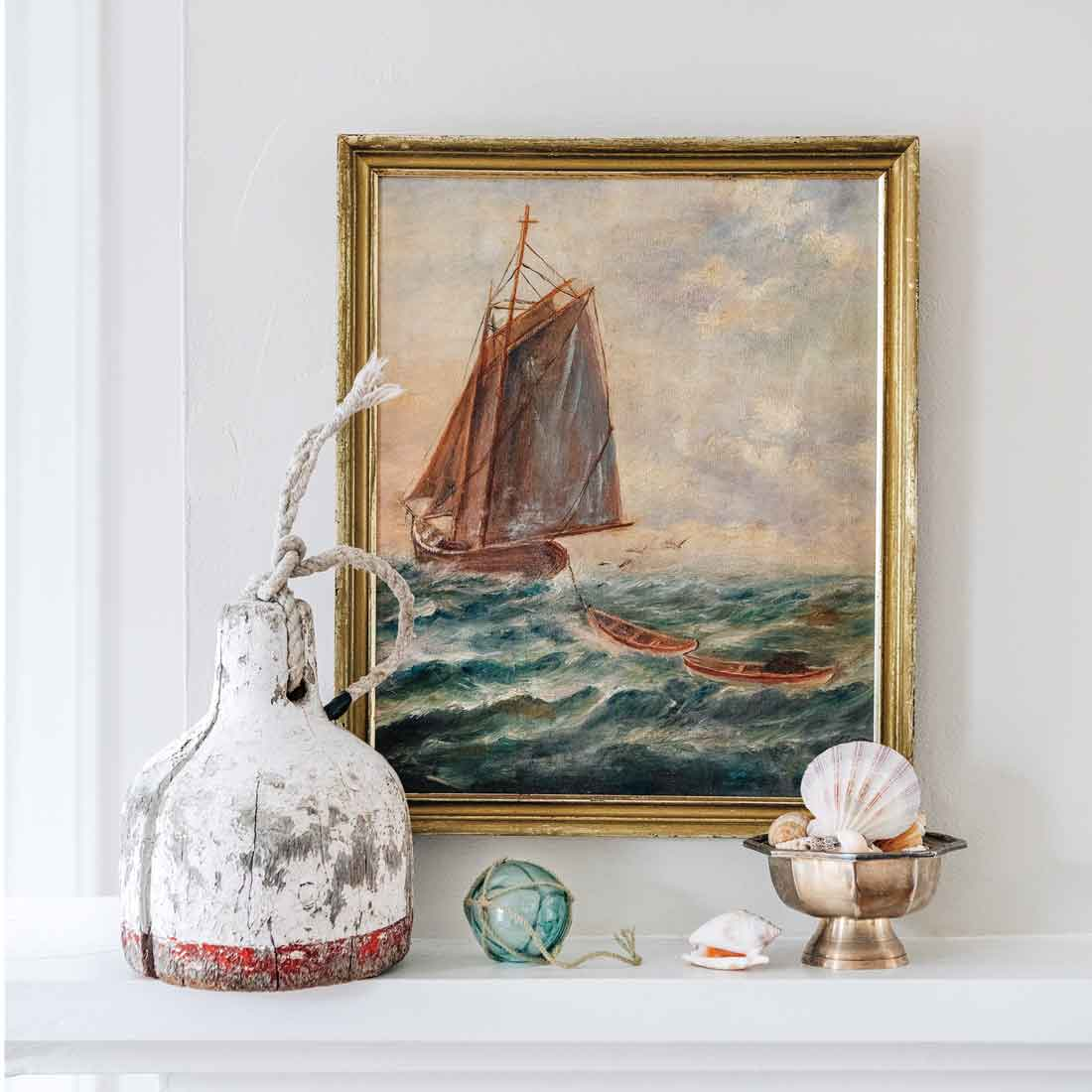 """Donovan was thrilled to find this unusual ship-and-dories scene, shown with a wooden buoy, Japanese fishing float, and silver dish. """"Put the right knickknacks in a group setting and it works,"""" she says."""