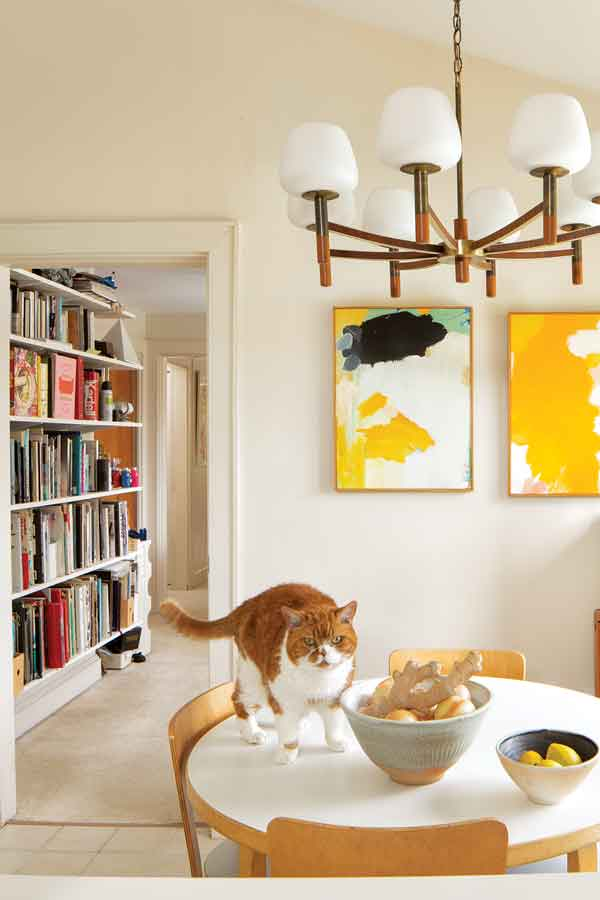 A 1978 Alvar Aalto dining set, a $2 church-fair chandelier, and acrylics by John in the kitchen.
